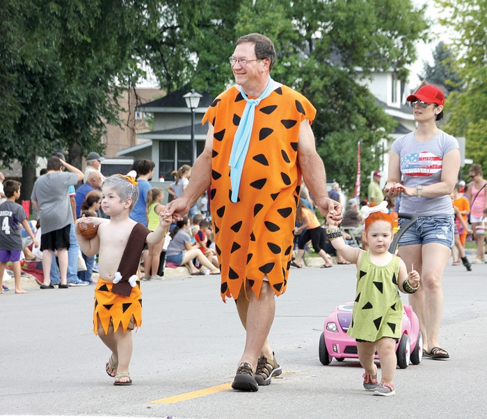 Ron Vadnais, as Fred Flintstone, walks in the 88th annual Benson Kid Day parade Saturday, July 21 with grandson Logan (Bamm Bamm) and granddaughter Lily (Pebbles) who are children of Ben and Alicia Vadnais.