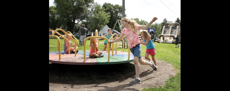 Kids play on a merry-go-round in the DeGraff city park during Labor Day festivities Sunday.