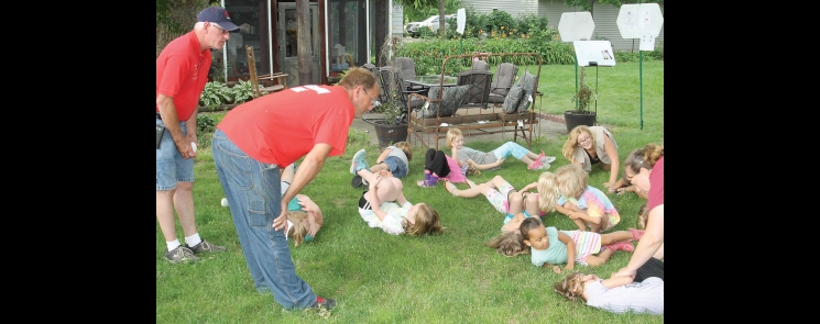 """Benson Firemen Dave Vollan (left) and Eric Tolifson watch as the young Girl Scouts practice the """"drop and roll"""" technique in case they ever caught fire."""