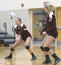 Megan Amundson (left) bumps up a serve during the Braves' section opening loss to Morris last week as Kelsey Pederson looks on from at right.  Photo courtesy of Brooke Kern, Morris Sun-Tribune.