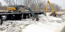 Burlington Northern Sante Fe and Riley Construction excavators work to clear ice floes from the Chippewa River at the BNSF railroad bridge next  to Minnesota Highway 9 West Sunday morning. As the ice was cleared, the river level dropped, reducing the flood threat to northwest Benson.