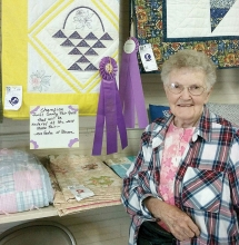 Mae Gades sits by her yellow quilt that won a grand championship ribbon at the Swift County Fair. She makes all kinds of quilts for all kinds of seasons and events.