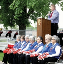 Benson City Council Member and veteran Lucas Olson addresses crowd at the Benson City Cemetery Memorial Day Service. Sitting in front are (right to left) VFW Ladies Auxiliary members Donna Christianson, Helen Hollingsworth, Tammy Luschen, Bev Klemm, Gail Bremher, Sue Hess, and Dee Cook.