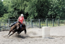 Miranda Nelson rides her horse around a barrel as she tries to set the winning time.