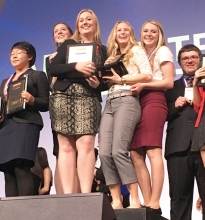 Benson High School students Courtney Johnson (second from left), Krista Hilleren, Hanna Lindblad, and Ashley Tolifson (second from right) on the awards podium after being announced as the National BPA champions.