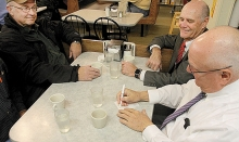 "Breen's fountain coffee regulars, from left, Paul Gandrud, Don Wilcox and Mark Kettelkamp play ""the numbers game"" for who will pay the bill."
