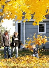 Jase Messenbrink runs gleefully through a cloud of leaves tossed by his grandmother Susan Casey.  He is the son of Lindsey Erickson and Jake Messenbrink of Benson. Jim Maus watches with a smile.