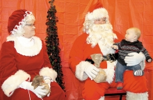 Mrs. Claus (Shirley Manska) and Santa (Karl Manska) pose with a young child during the Santa Truck's visit to the Benson Fire Hall, Monday.  All the kids had a great time visiting with Santa and Mrs. Claus and each received a bag of treats.